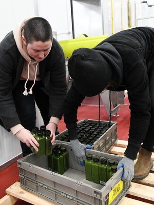 Jenny, kiri, dan Jessie James, saudara perempuan dan salah satu pendiri Drought Juice, memuat botol jus organik yang telah melalui mesin HPP.