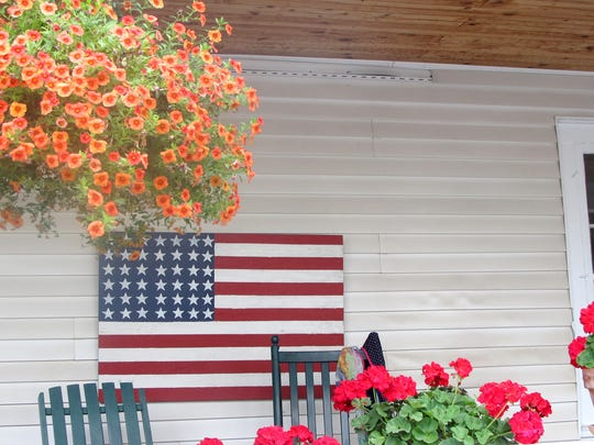 A U.S. flag shares porch space with summer flowers Tuesday on South Winooski Avenue in Burlington. Photographed Tuesday, July 1, 2014.