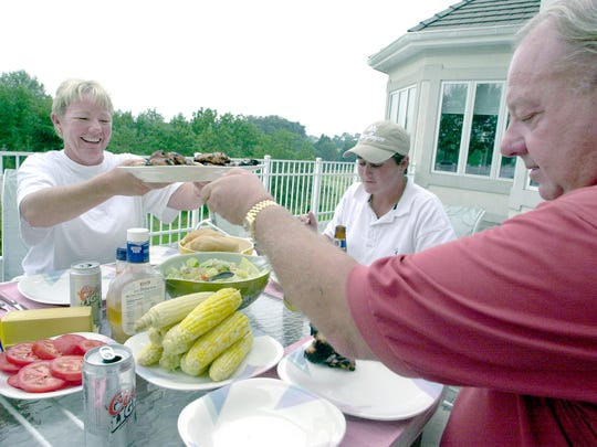 In August 2000, Dale Anstine, right, passes a plate of chicken to Wendy Doolan who tours with the LPGA at his home near Honey Run Golf Club. Anstine made friendships with golfers over the years opening his home to members of the York Futures Classic. Michelle Ellis of Sydney, Australia is pictured in the background.