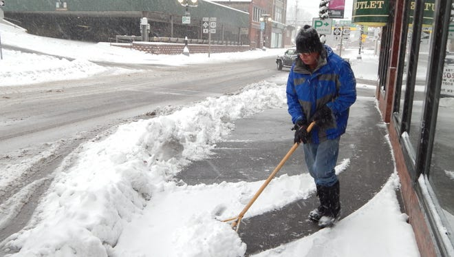 Alan Messner shovels the sidewalk in front of Surplus Outlet in downtown Houghton, Mich., Tuesday after an early season storm in Copper Country, closing schools and forcing the cancellation of some Veterans Day activities. As much as 3 feet of snow blanketed parts of Michigan's Upper Peninsula, with temperatures in the 20s and 30s early Wednesday.
