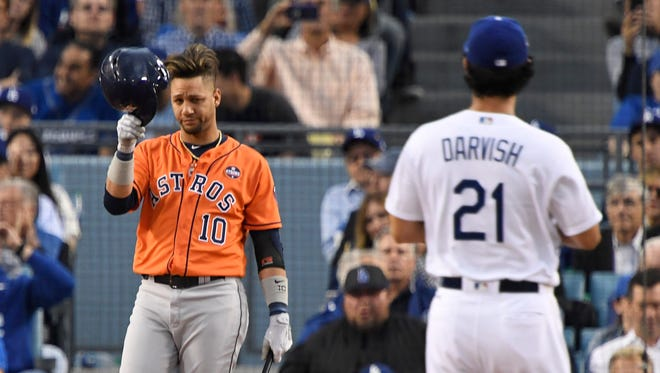 Astros' Yuli Gurriel tips his hat as he gestures to Dodgers starting pitcher Yu Darvish.