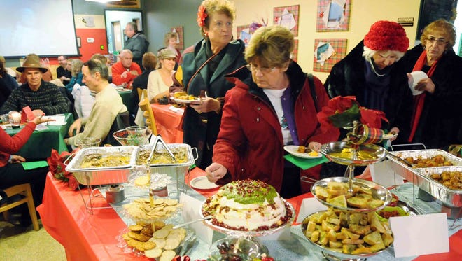 Karen Smith, of Algonac, reaches for a treat from the spread at Sue's Coffee House with Pam Pam Lauer, of Fair Haven, left, and Carolyn Henderson, of Anchorville, right, during a Gourmet Gallop in St. Clair.