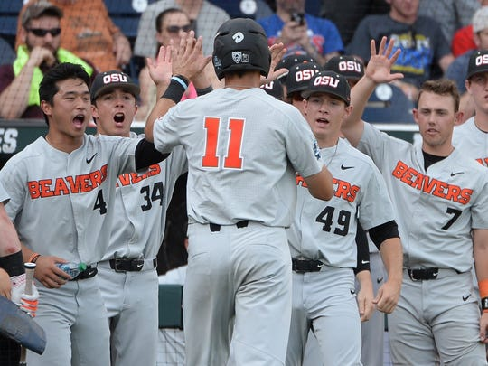 Jun 28, 2018; Omaha, NE, USA; The Oregon State Beavers celebrate a run scored by right fielder Trevor Larnach (11) during the first inning against the Arkansas Razorbacks in game three of the championship series of the College World Series at TD Ameritrade Park. Mandatory Credit: Steven Branscombe-USA TODAY Sports