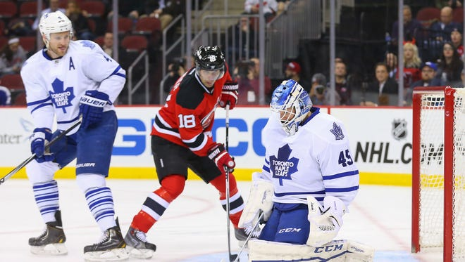 Toronto Maple Leafs goalie Jonathan Bernier (45) makes a save while New Jersey Devils right wing Steve Bernier (18) looks for the rebound during the second period at Prudential Center.