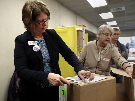 Outagamie County Clerk Lori O'Bright opens a box of