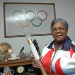 Mamie Rallins holds an Olympic torch used during the 1996 Olympics in Atlanta in front of an Olympic banner that hangs on the wall in this 2008 photo. Rallins died in a car crash on Monday.