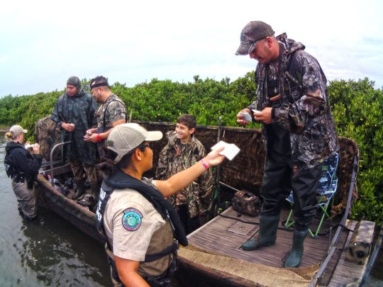 Notice the smile on the young hunter's face, indicating the pleasant nature of this game warden interaction with hunters. I believe game warden Albert Flores was teasing the boy about their lack of birds.