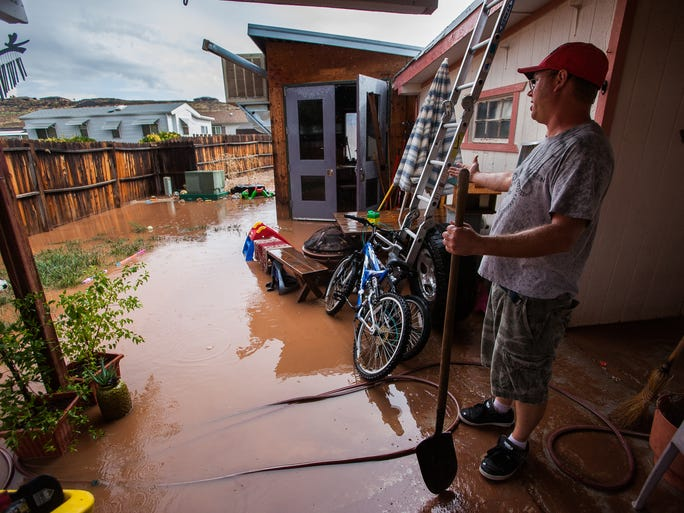 A resident surveys the damage from a flash flood in Washington City on July 12, 2013.