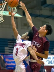 Las Cruces High's Markus Collins finishes the fast break and gets fouled from behind by Deming's Alex Villa during Tuesday night's district tournament game at LCHS.