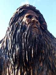 A wood Sasquatch made by Kevin Stauslin rests outside