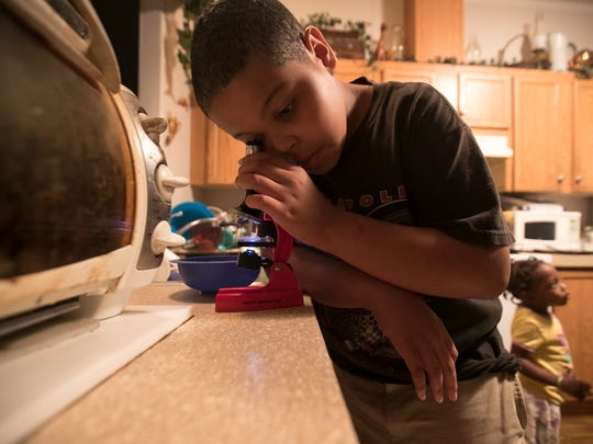 Tovanni Anderson, 8, peers into a microscope to examine why his grandmother's well water in Charleston Park is bad. Her water has tested positive for bacteria.