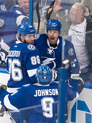 Tampa Bay right wing Nikita Kucherov, left, center Alex Killorn, and center Tyler Johnson celebrate the game winning goal by Killorn in the third period.