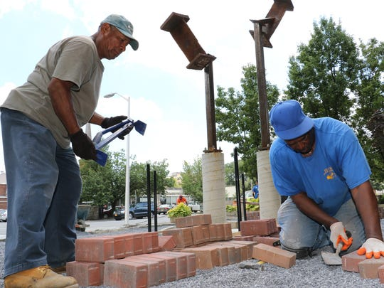 From left, Tomas Marcial, 60, and Jimmy Floyd, 67, lay bricks for Poughkeepsie City Hall's September 11th memorial on Tuesday.
