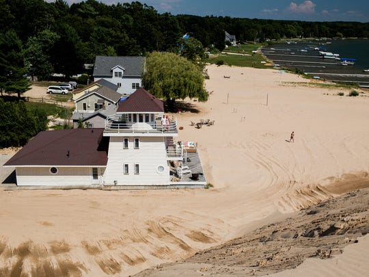 David Dressler and his wife Sue of Chicago, Ill. pose for a portrait on the balcony of their cottage facing the approximate 150-foot tall dune that swallowed one of their two cottages in April at the edge of the Silver Lake State Park in Mears, Mich.