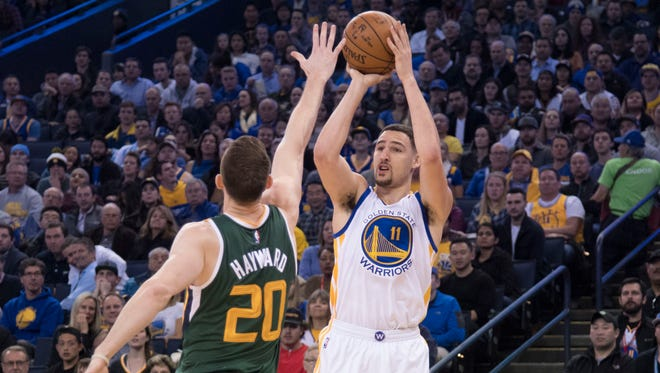 Golden State Warriors guard Klay Thompson (11) shoots the basketball against Utah Jazz forward Gordon Hayward (20) during the second quarter at Oracle Arena.