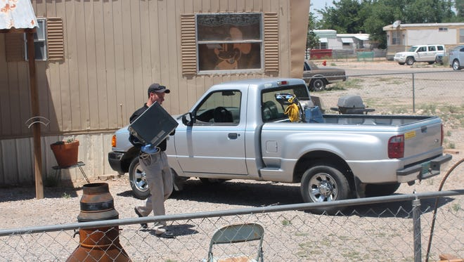 An Alamogordo police officers carries one of several computers siezed from a home in the 1100 block of Lindberg Avenue Friday. Michael Wallace is charged with exploitation of children.