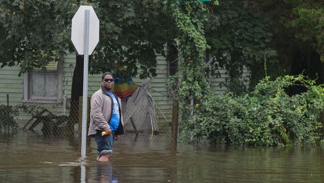 A man stands in floodwater along the corner of Rose Street and Delaware Avenue on Friday.