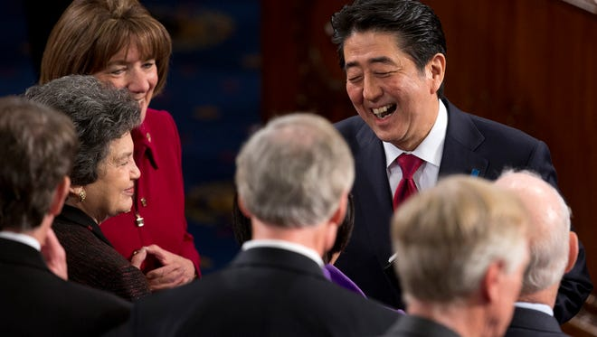 Japanese Prime Minister Shinzo Abe is greeted by members of Congress after speaking to a joint meeting of Congress on Wednesday, April 29, 2015.