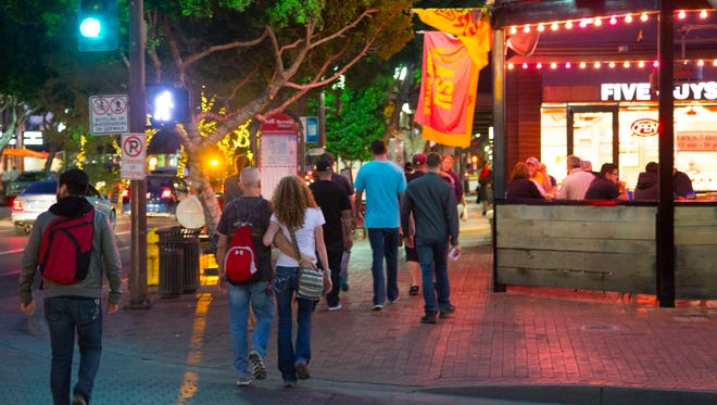 People make their way on Mill Avenue in Tempe, AZ on Thursday, Nov. 13, 2014. The downtown has gone through rebranding.