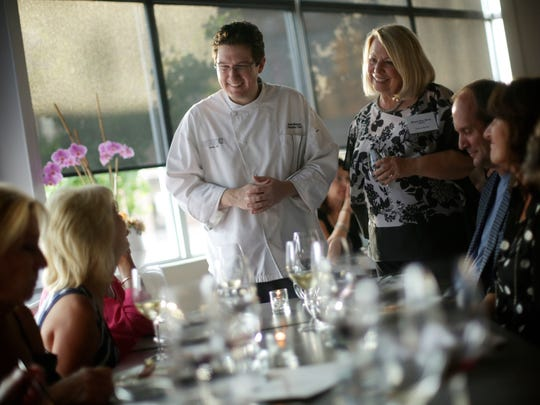 Bistro 82 chef Derik Watson, left, and Detroit Free Press Restaurant Critic Sylvia Rector chat with guests during the Detroit Free Press Top 10 Takeover dinner series at the Bistro 82 in Royal Oak, MI, on Monday, August 10, 2015.