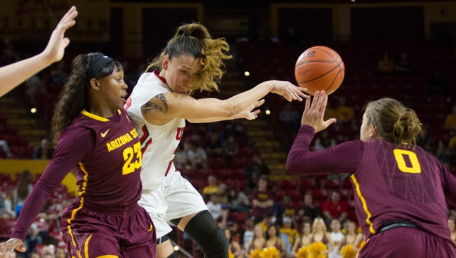 Utah's Danielle Rodriguez passes away from a double-team from ASU's Elisha Davis (23) and Katie Hempen (0) at Wells Fargo Arena in Tempe, AZ on February 27, 2015.