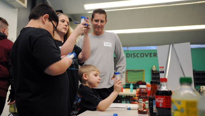 Isaac White-Jackson, 10, left, Ashley Jackson, center left, Ian Jackson, 5, and Kevin Jackson work together to match the sugar content to different drinks during the Family Fit program Wednesday at the Ross County YMCA.