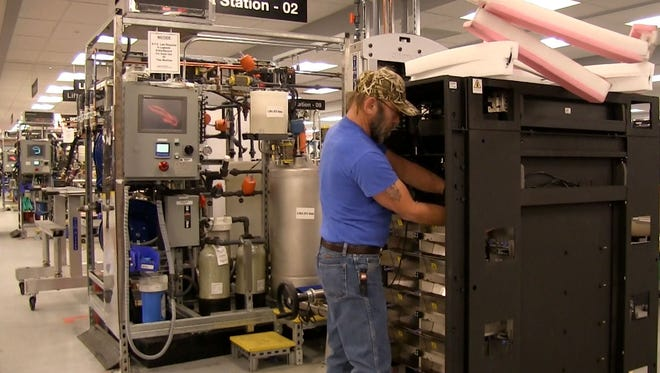 Gary Smith, a production specialist at IBM's Poughkeepsie plant, works on a z13 mainframe computer in IBM's Poughkeepsie plant.