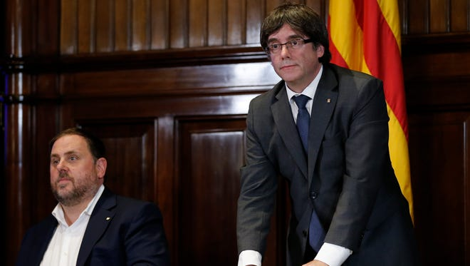 President of the Catalan Government Carles Puigdemont, right, signs a decree calling for an  independence referendum at the Catalan Parliament in Barcelona, on Sept. 6, 2017.