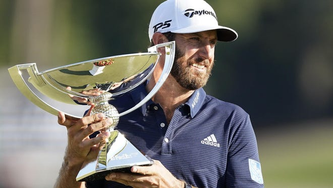 Dustin Johnson holds up the FedEx Cup trophy after winning the Tour Championship golf tournament on Monday, Sept. 7, 2020 at Lake Golf Club in Atlanta.