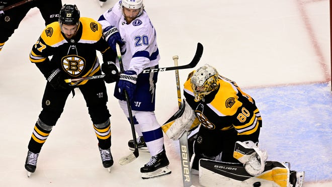 Bruins goaltender Dan Vladar makes a pad save as Bruins defenseman John Moore (27) and Lightning center Blake Coleman (20) look on during the third period in Wednesday's night's Game 3 of the teams' second-round series.