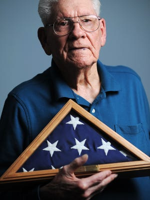 Ken Salisbury, 92, holds an American flag that he has in recognition of his support of Honor Flights.