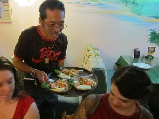 Chang Liampetchakul, owner of Tipps Thai Cuisine in downtown Ventura, serves salads to diners during a meal in 2014.