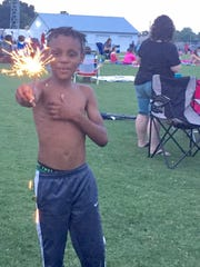 In this Tuesday, July 4 photo, Harlem Peteck, 8, of Salisbury, plays with a sparkle at the Wicomico County Stadium in Salisbury while waiting for the start of the Red, White & Boom fireworks display. Several hundred people attended.