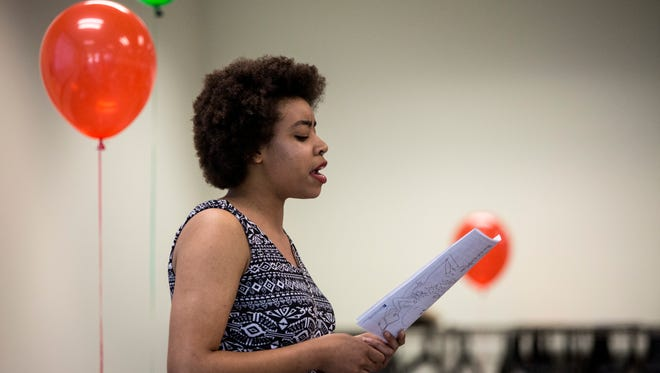 Lanesha Stanley, of Port Huron, reads a poem to the audience during the Juneteenth celebration Friday, June 17, 2016 at the Donald Dodge auditorium in the St. Clair County Administrative Building in Port Huron.