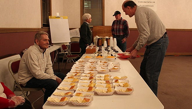 Dennis Theaker, brother of Mansfield Mayor Tim Theaker, volunteers at St. John's United Church of Christ's annual chili dinner while Dean Earl of Mansfield serves himself some cornbread Sunday, Dec. 25, 2016. This is the fourth year the church hosted the Christmas dinner.