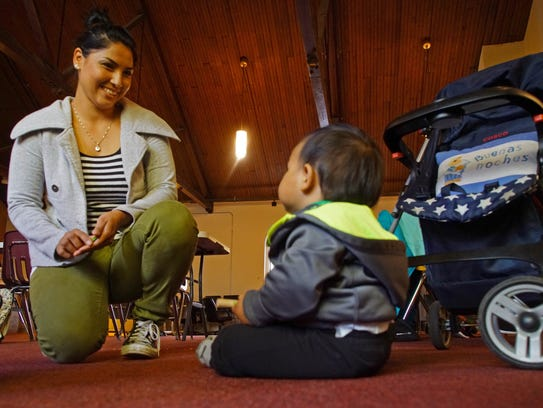 Carolina Lopez, 26, plays with her one-year-old son