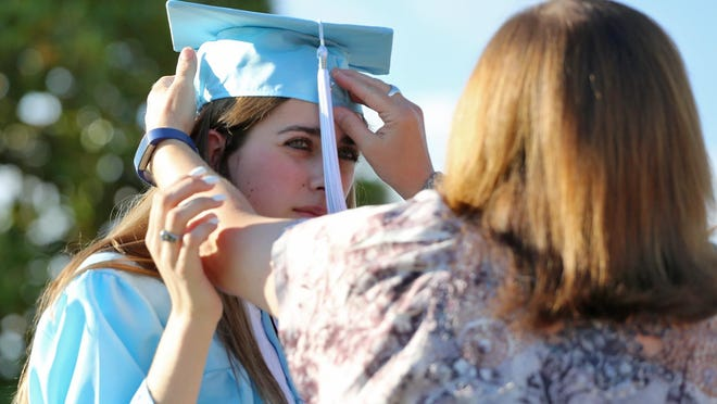 Montana Earl gets help with her cap from mom Tanya before the start of Burns High School's graduation on Thursday.