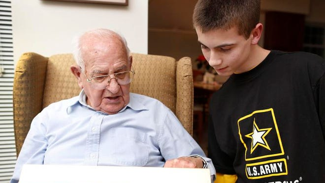 Patrick Gurnow, a student at Webster Schroeder, speaks with Jack Tuttle in Webster. Tuttle fought in World War II with the Army's 4th Infantry Division, and Patrick is documenting Tuttle's wartime experiences.