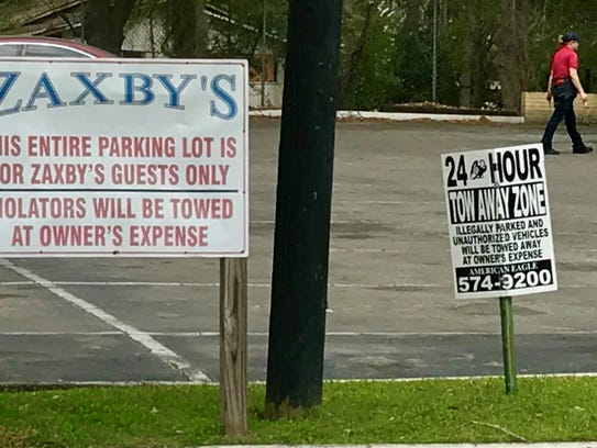 Tow-away signs in the Zaxby's parking lot on West Tennessee