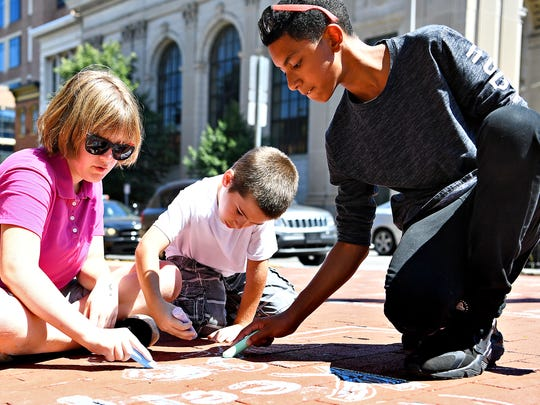 Ashley Senter, 12, left, Zachary Swoyer, 9, center, and Richard Morel, 12, write messages of love and positivity for the city in sidewalk chalk in Continental Square during the first week of the York City School District Police Department's SAFE Camp in York City, Thursday, July 12, 2018. Dawn J. Sagert