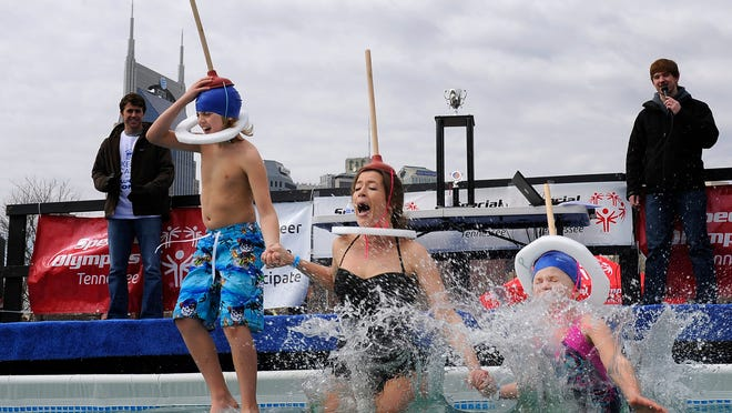 "Amy Parker with her kids Jonah and Jacklyne, the ""Parker Plungers"" jump into a cold pool for the Polar Plunge to benefit Special Olympics outside LP Field on Saturday in Nashville."