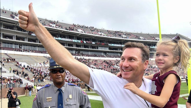 Mississippi State Bulldogs head coach Dan Mullen celebrates with his daughter Breelyn after defeating the Massachusetts Minutemen at Davis Wade Stadium.