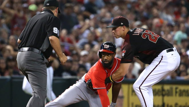 Diamondbacks Jake Lamb (22) applies a tag to Nationals Brian Goodwin (8) in the fifth inning at Chase Field in Phoenix, Ariz. on July 22, 2017.