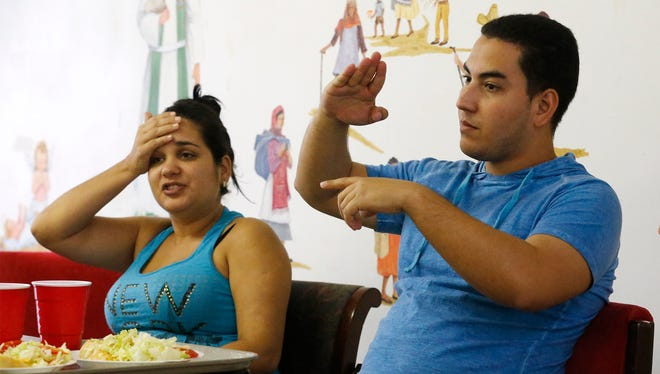 Alina Miranda Guinado, 27 and Javier Menway Barcia, 24, sit Wednesday in the San Pablo Lutheran Mission conference room and discuss the obstacles they faced getting to El Paso from Cuba.