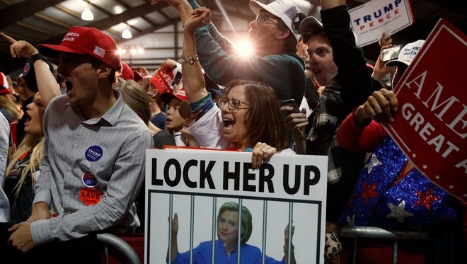 """In this Monday, Nov. 7, 2016 photo, supporters of Republican presidential candidate Donald Trump, one holding a sign that reads, """"LOCK HER UP,"""" cheer during a campaign rally in Leesburg, Va. Trump, the president-elect, is calling for unity in words that draw attention precisely because they sound so unlike Trump, the candidate. But many question whether it is possible to reverse the campaign's damage to political discourse and its ripples out to the way Americans speak to and about each other."""