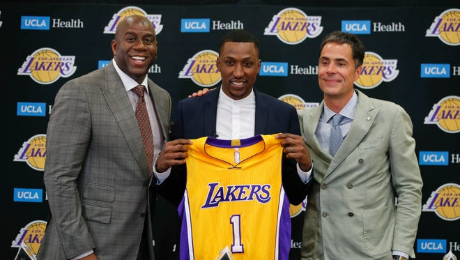 Lakers guard Kentavious Caldwell-Pope, center, poses for photos with Magic Johnson, left, and Rob Pelinka during a news conference July 18, 2017 in Los Angeles.