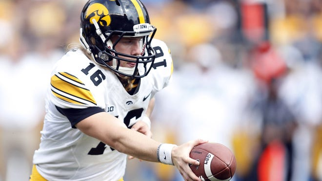 Iowa quarterback C.J. Beathard hands the ball off against the Pittsburgh Panthers during the third quarter Saturday at Heinz Field. The Hawkeyes won 24-20.