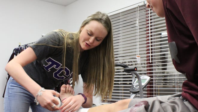 Hawley High School sophomore McKayla Olney tapes a student-athlete Wednesday afternoon. Olney last summer won a taping competition at a camp at Texas Christian University.