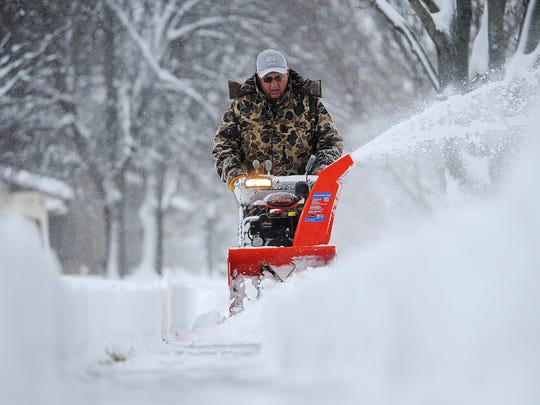 Harvey Wollman, of Sioux Falls, uses a snow blower to clear the sidewalk near his house during the first snow of the season Friday, Nov. 20, 2015, in Sioux Falls.