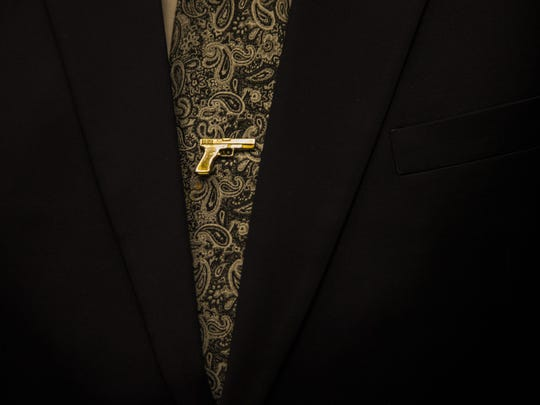 The sheriff is no fashion plate, but he favors sports jackets and this old-fashioned tie tack in the shape of a  pistol.